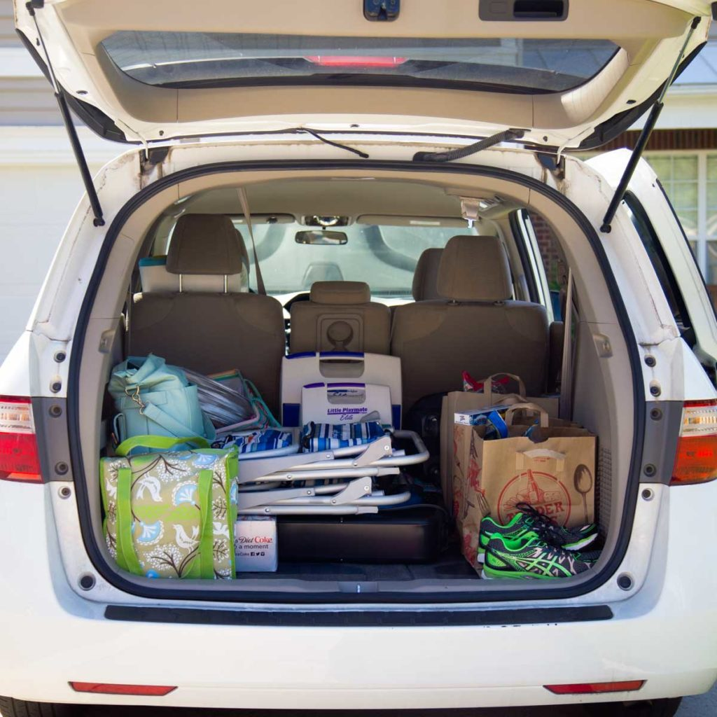The back of a mini van is open so you can see all the items packed for a family vacation.