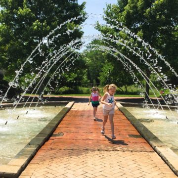 Two young girls run under the arched fountain at the Daniel Stowe Botanic Garden.