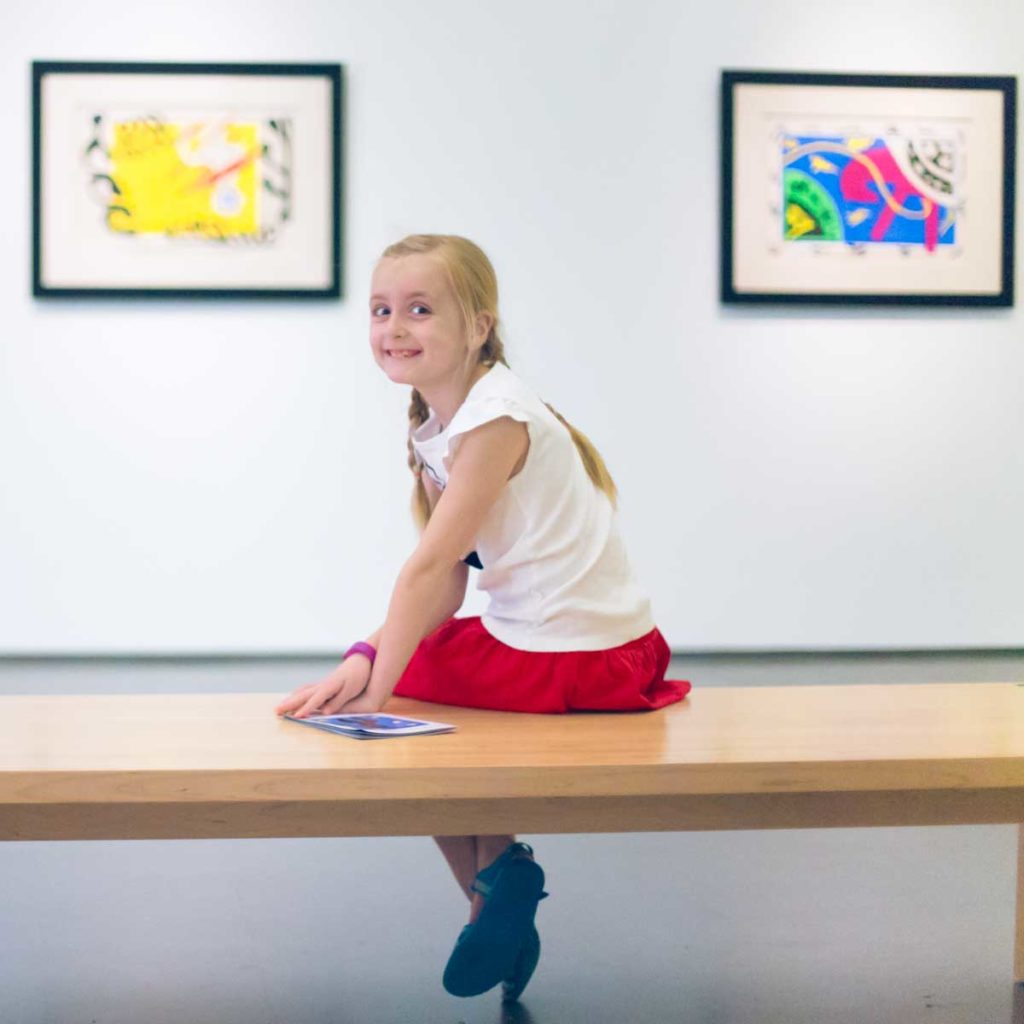 A young girl sits on a bench at Charlotte's Mint Museum.