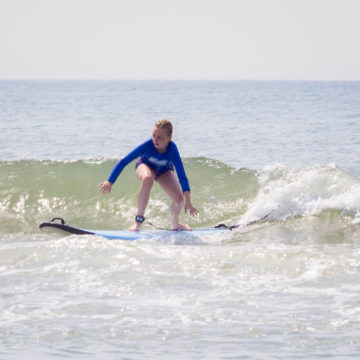 A young girl in a blue shirt is surfing with a wave behind her.