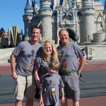 Angie and her family in front of the Disney castle.
