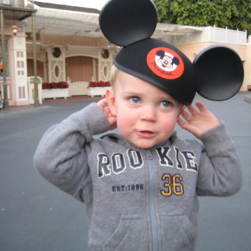 Mary Beth's son is wearing a Mickey ear hat at the parks.