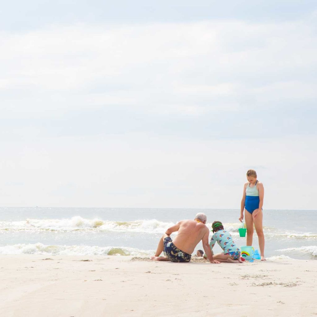 A grandpa and two girls make sandcastles on the beach.