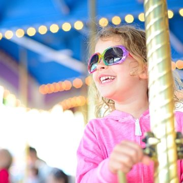 Carey's daughter rides the carousel at Disney World in Florida.
