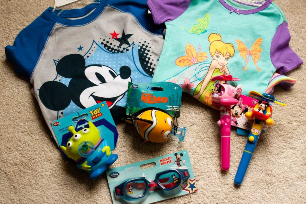 Disney jammies and little souvenir toys sit in a pile before a trip.