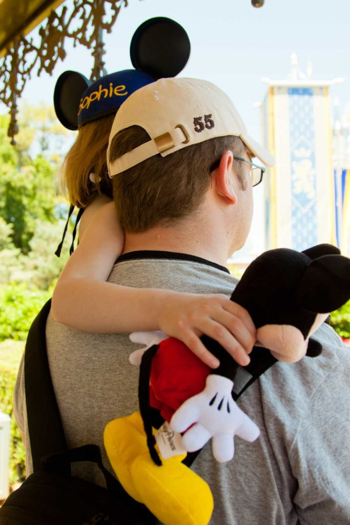 A dad holds his young daughter up high so she can see the Disney parade better.