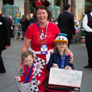A Disney runner at the finish line with her kids holding cheer signs.