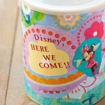 A cute tub has been decorated with papers to become a Disney savings jar.