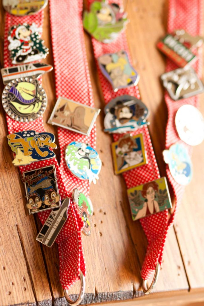 Two red and white polka dot lanyards have Disney trading pins covering them.