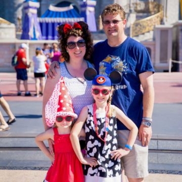 A family of four stands in front of the Disney castle in Florida.