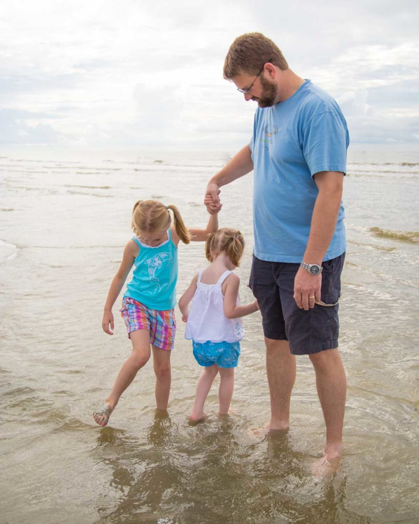 Two girls test out the water of a tide pool with their dad watching carefully.