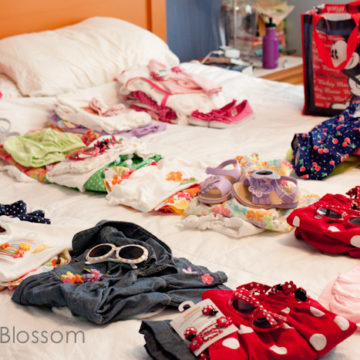 Piles of kids' clothing sits on a bed ready to be packed into a suitcase.