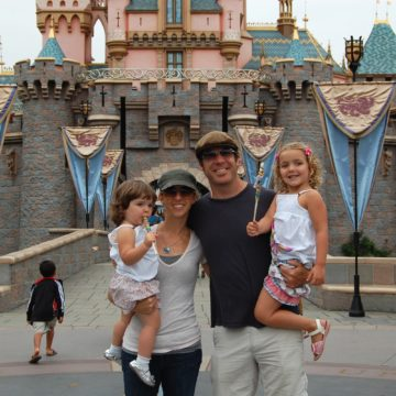 Rachelle's family standing in front of the Disneyland castle in California.