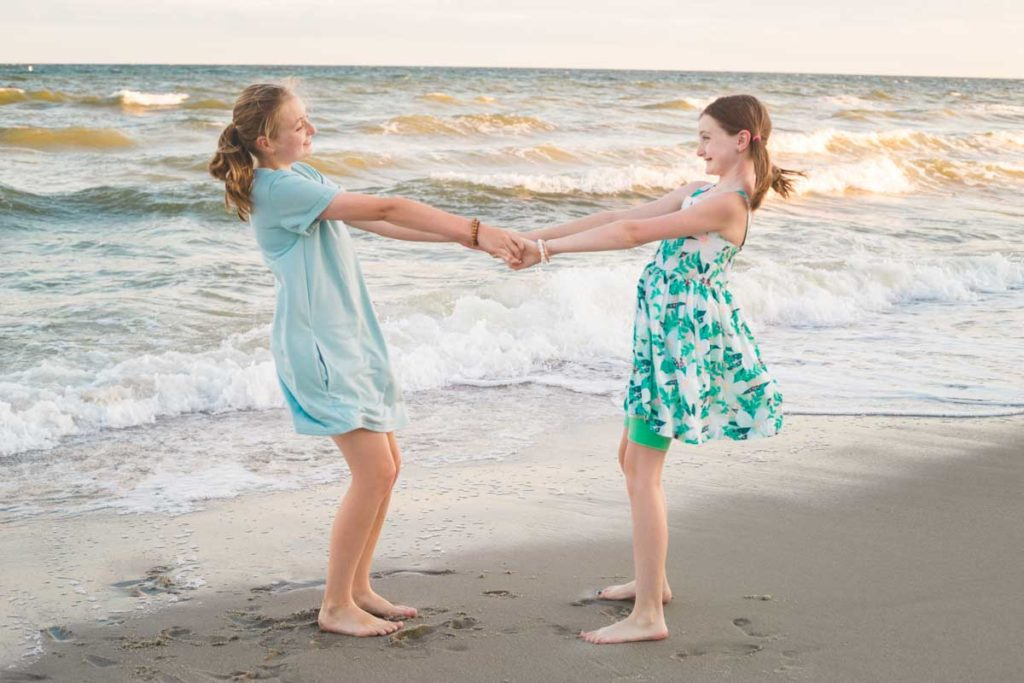Two sisters hold hands by the ocean for a family photo.