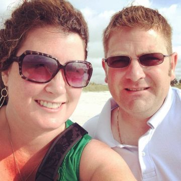 A husband and wife on the beach during a romantic getaway.