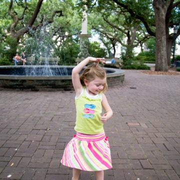 A young girl twirls by a fountain in Savannah, GA