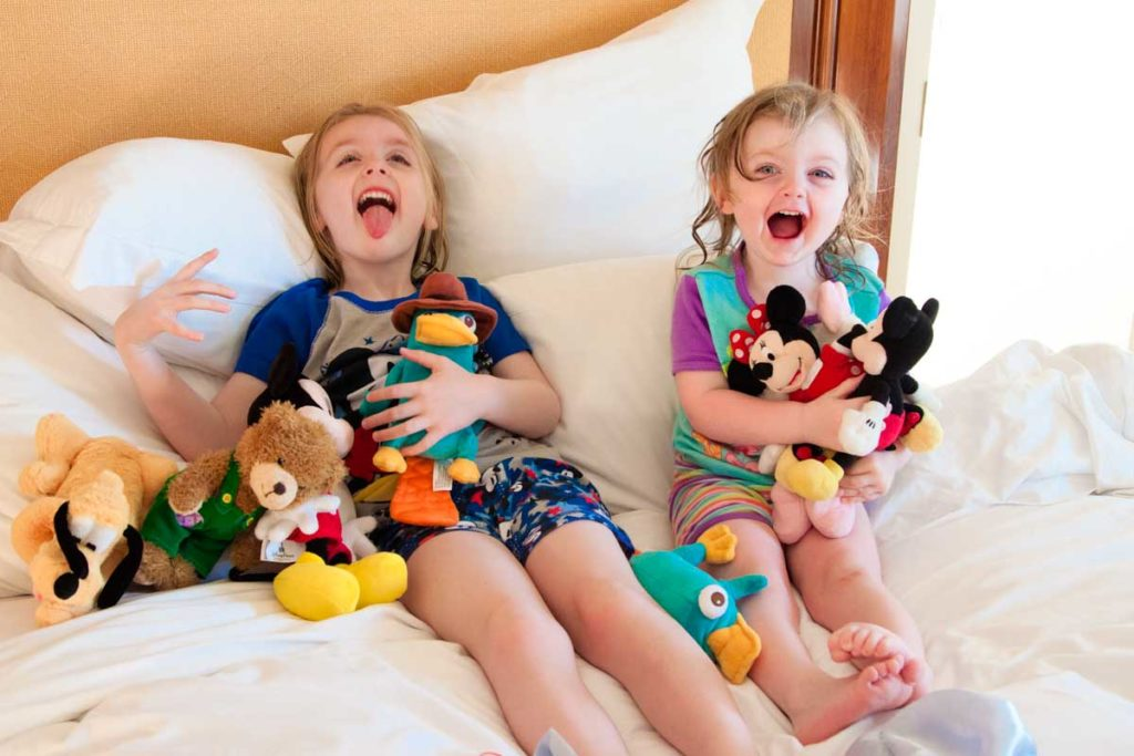 Two young girls are goofing around with a pile of stuffed animals.