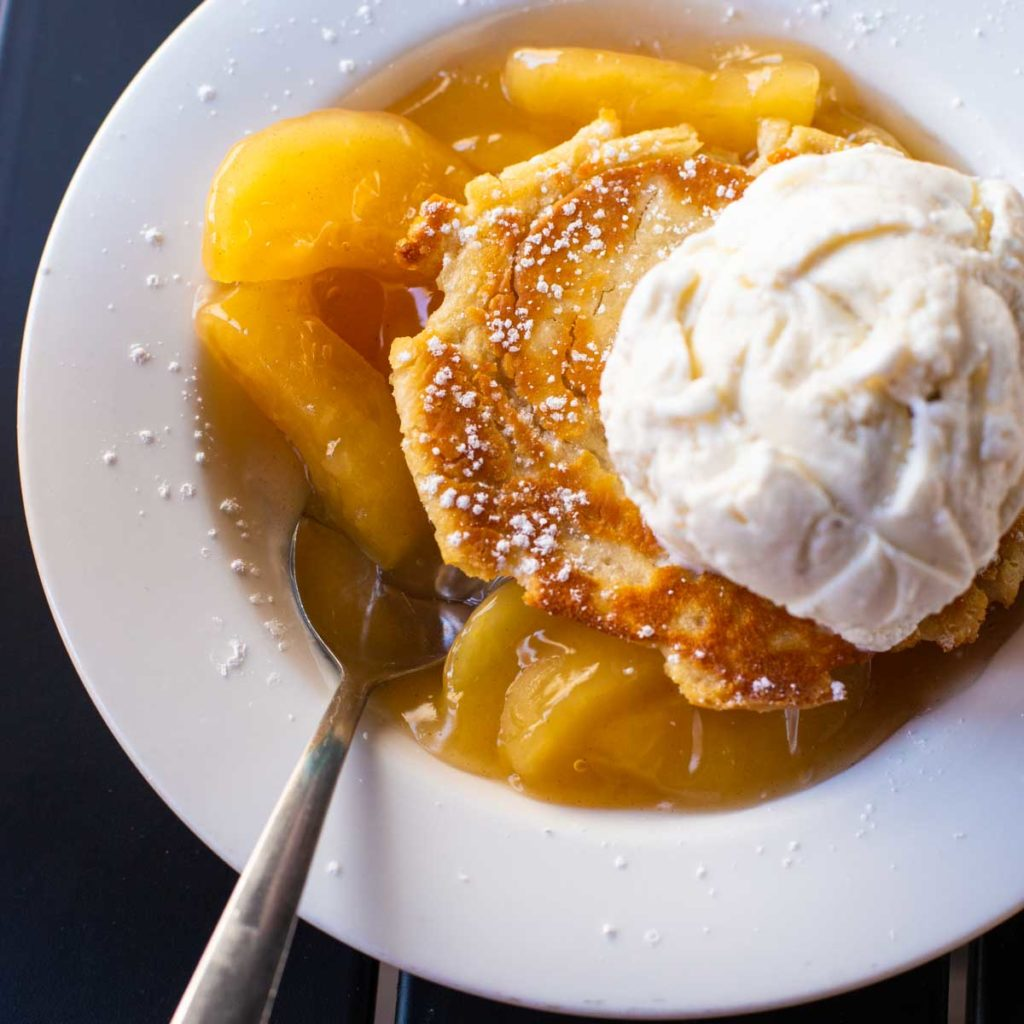 A bowl full of apple sonker with vanilla ice cream on top.